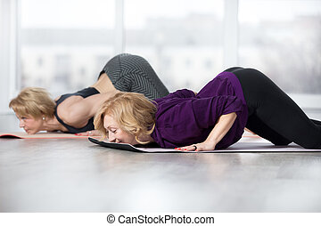 Senior women doing Ashtanga Namaskara pose - Fitness,...