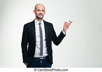 Smiling handsome businessman standing and pointing away over...