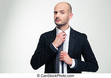 Handsome confident young business man straightening his tie...
