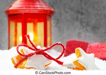 Cinnamon stars and red lantern in the snow