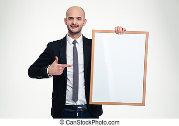 Confident business man holding blank board and pointing on...