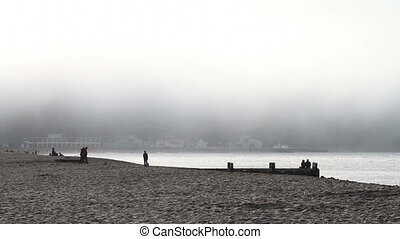 Sandy Beach with Fog and People