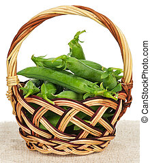 Fresh peas pods in a wicker basket on straw mat over white...