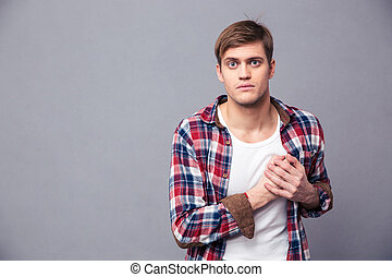 Stunned dazed man in checkered shirt with hand on chest -...