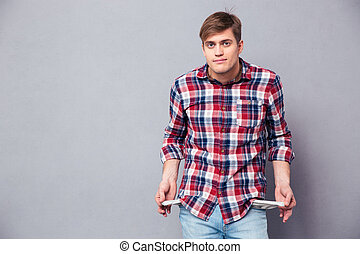 Poor handsome young man in checkered shirt showing empty...