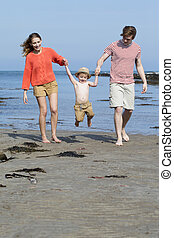 Happy Little Family - Young two parent family at the beach...