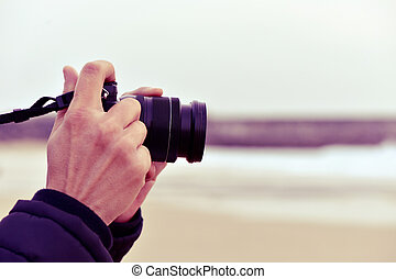 young man taking a picture in front of the sea - closeup of...
