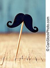 felt mustache in a stick on a wooden surface - a felt...