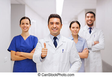 medics or doctors at hospital showing thumbs up -...