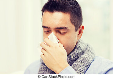 close up of ill man with flu blowing nose at home -...