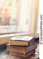 Old books on windowsill - Stack of old books laid on...