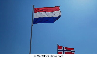 Flags of Netherlands and Norway on poles with blue sky...