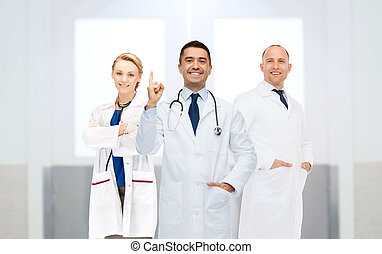 group of doctors at hospital pointing finger up -...