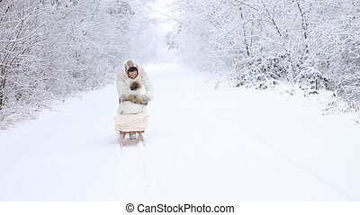 Mom baby rolls on a sled in the winter forest