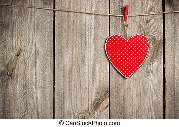Red heart hanging on the clothesline for Valentine Day -...
