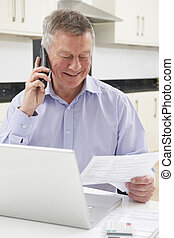 Senior Man On Phone Checking Personal Finances