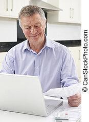 Smiling Senior Man Checking Finances On Laptop