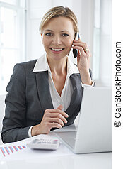 Businesswoman Working At Desk On Mobile Phone