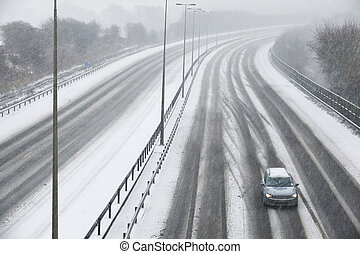 Single Car On Motorway During Snow Storm