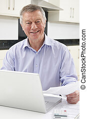 Smiling Senior Man Checking Home Finances