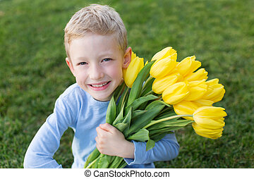 spring time - smiling beautiful boy holding blooming yellow...