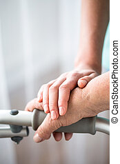 Young and old hand on walking frame