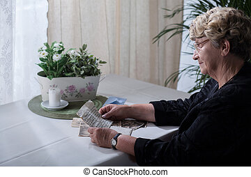 Widow looking over memorabilia - Picture of smiling widow...