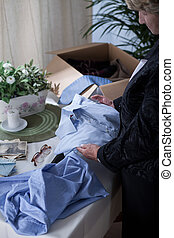 Widow packing things of husband - Picture of miserable...