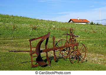 Rusty plough on the green grass near farm house in...