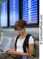 Lady waiting in airport terminal using phone - Lady with...