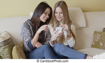 Couple of beautiful girlfriends using mobile phone while...