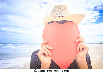 Guy in Hat Hides Face behind Hand-made Red Heart on Beach -...