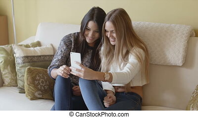 Two excited young woman reading an sms or text message on a...