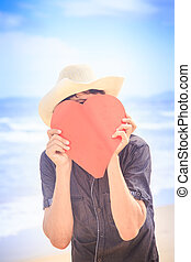 Guy in Hat Hides Face behind Hand-made Red Heart - closeup...