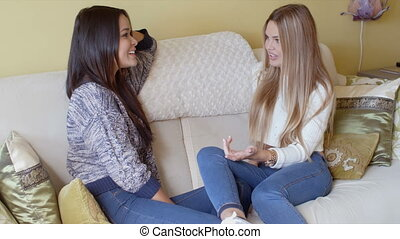 Two young woman enjoying a chat as they laugh and smile...