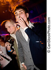 Young man smoking in the nightclub - European man smoking a...