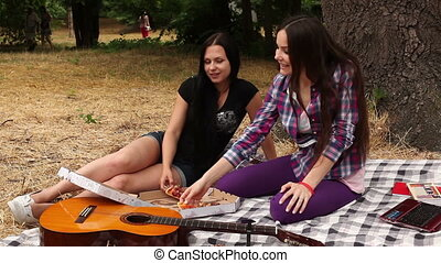 Girls eating pizza in the Park - Two girls sit in the shade...