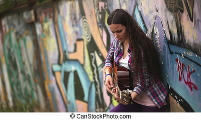 The girl with the guitar against a wall with graffiti