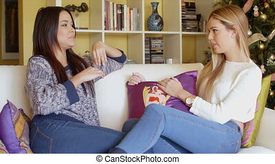 Two young woman relaxing chatting at home