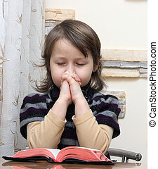 prays - little girl prays over the open bible
