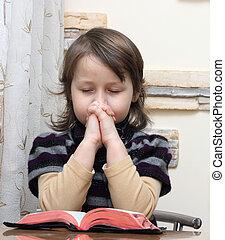 prays  - little girl prays over the open bible