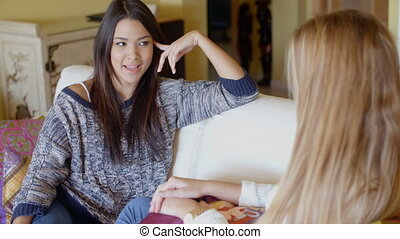 Two young woman relaxing chatting at home in the living room...
