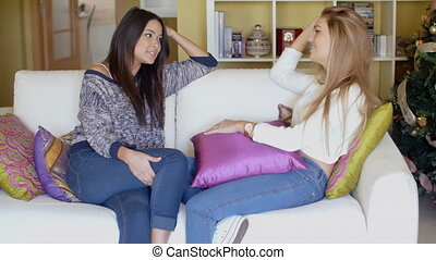 Two adorable girls sitting on couch and talking