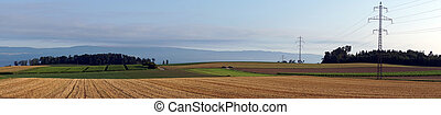 Farm field - Panorama of pylons with electrical wire on the...