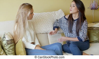 Two young girlfriends sharing their news having a serious...