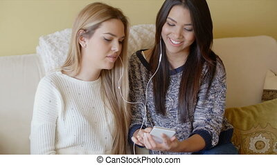 Two beautiful girls on couch listen to music with one pair...
