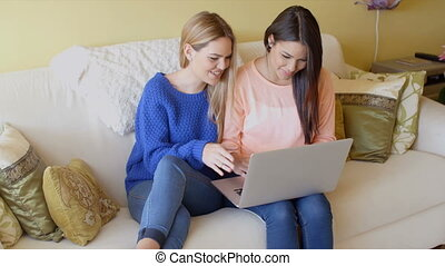 Two happy young women browsing the internet - Two happy...