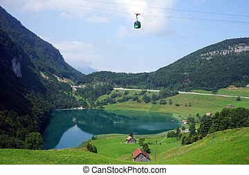 Cable car and farm houses near lake in Switzerland