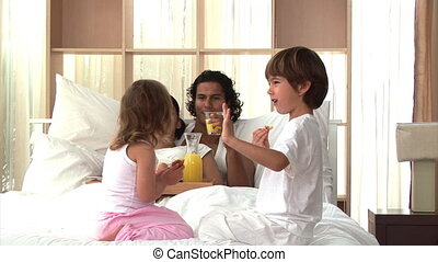 Relaxed family having breakfast sitting on bed at home