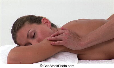 Blond woman enjoying a back massage in a spa center